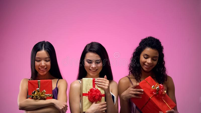 Beautiful ladies looking at giftboxes in hands, best present for friend, holiday stock photos