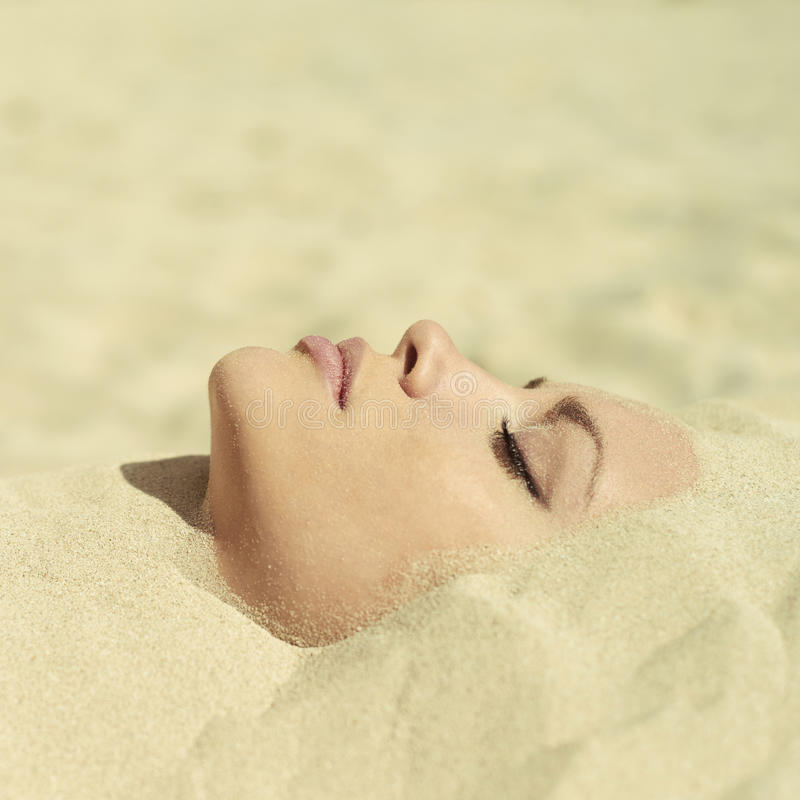 Beautiful lady buried in the sand. Art photo of beautiful lady buried in the sand royalty free stock photo