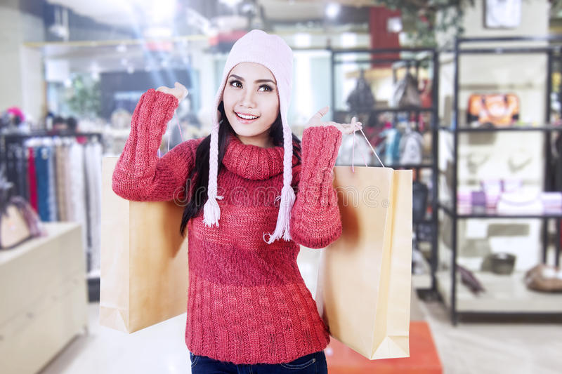 Beautiful lady carry shopping bags in mall. Beautiful woman with beany and jumper carry brown shopping bags in the mall royalty free stock images