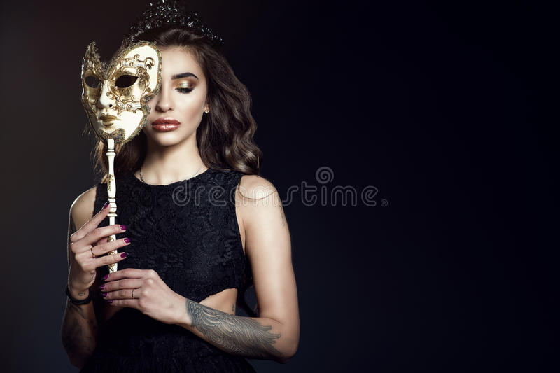 Beautiful lady with closed eyes hiding the half of her face behind the Venetian mask stock photos