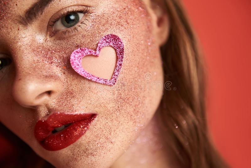 Beautiful lady with creative make up and heart-shaped sticker on face royalty free stock photography