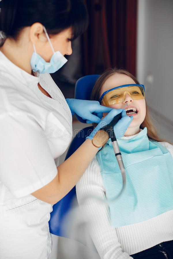 Beautiful girl sitting in the dentist`s office. Beautiful lady in the dentist`s office. Woman in a uniform royalty free stock photo