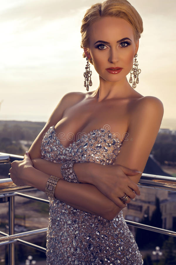 Beautiful lady in elegant dress posing at balcony royalty free stock images