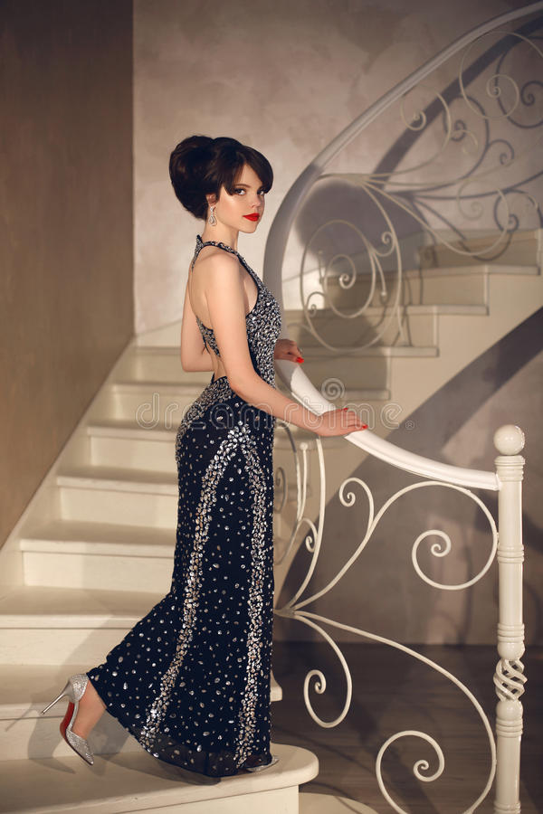 Beautiful lady in fashion dress posing on front staircase. Elegant brunette woman in long gown. Attractive girl model with r royalty free stock images