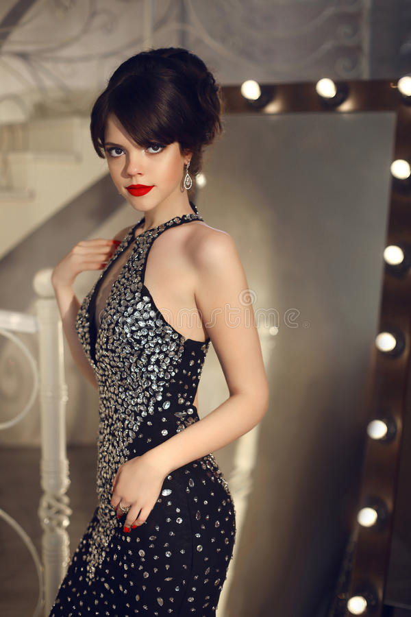 Beautiful lady in fashion dress posing by mirror with light bulb royalty free stock photo