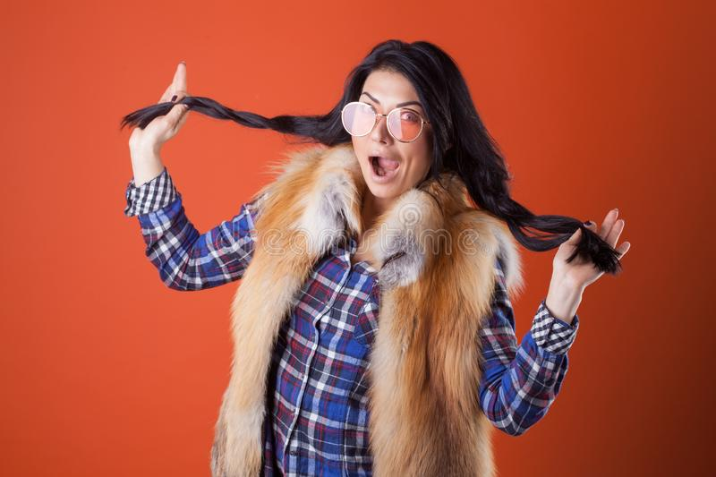 Pretty woman model pose wear plaid shirt and fur vest on the orange studio background royalty free stock photo