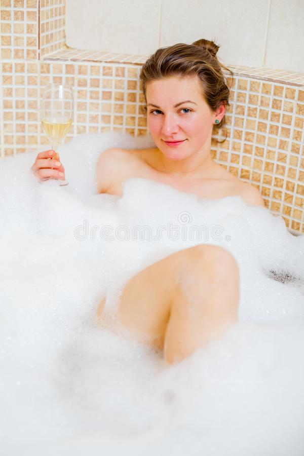 Elegance woman in the tub with champagne stock images