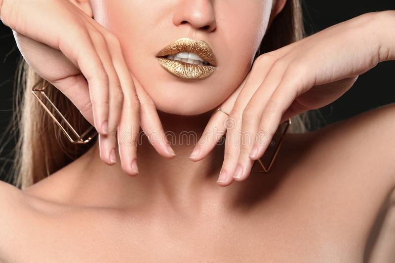 Beautiful lady with gold shiny lipstick. Closeup royalty free stock images