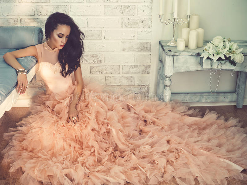 Beautiful lady in gorgeous couture dress sitting on the floor. Fashionable portrait of beautiful lady in gorgeous couture dress sitting on the floor royalty free stock photography