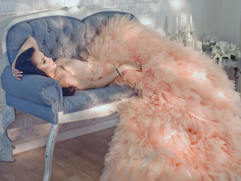 Beautiful lady in gorgeous couture dress on sofa. Fashionable portrait of beautiful lady in gorgeous couture dress on sofa royalty free stock image