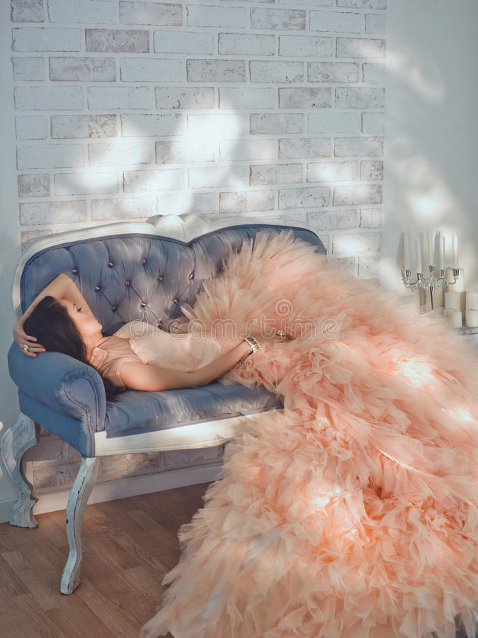Beautiful lady in gorgeous couture dress on sofa. Fashionable portrait of beautiful lady in gorgeous couture dress on sofa royalty free stock images