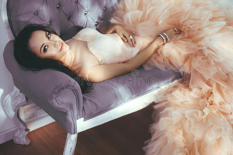 Beautiful lady in gorgeous couture dress on sofa. Fashionable portrait of beautiful lady in gorgeous couture dress on sofa stock photos