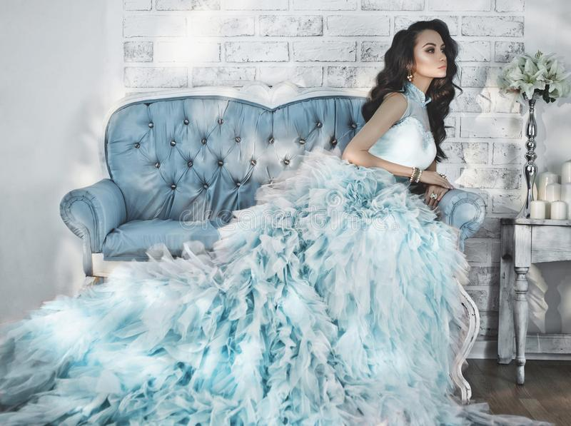 Beautiful lady in gorgeous couture dress on sofa. Fashionable portrait of beautiful lady in gorgeous couture dress on sofa. Holidays & Events. Evening dress stock photos
