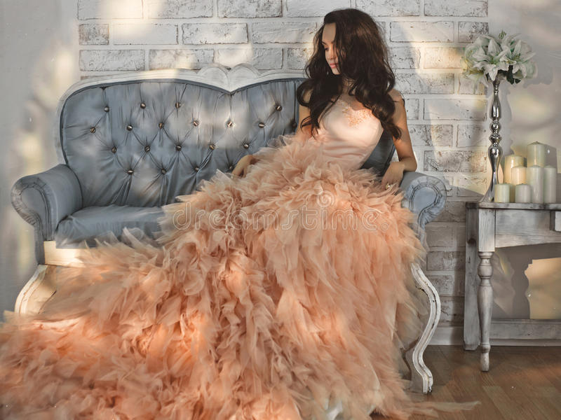 Beautiful lady in gorgeous couture dress on sofa. Fashionable portrait of beautiful lady in gorgeous couture dress on sofa. Holidays & Events. Evening dress stock image