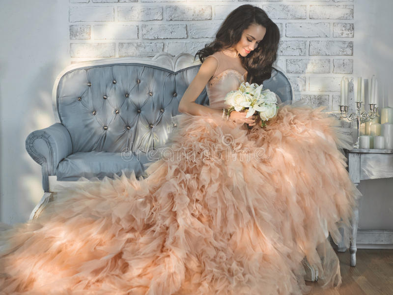 Beautiful lady in gorgeous couture dress on sofa. Fashionable portrait of beautiful lady in gorgeous couture dress on sofa. Holidays & Events. Evening dress royalty free stock image