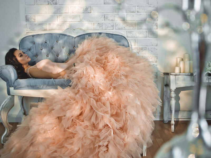Beautiful lady in gorgeous couture dress on sofa. Fashionable portrait of beautiful lady in gorgeous couture dress on sofa. Holidays & Events. Evening dress royalty free stock images