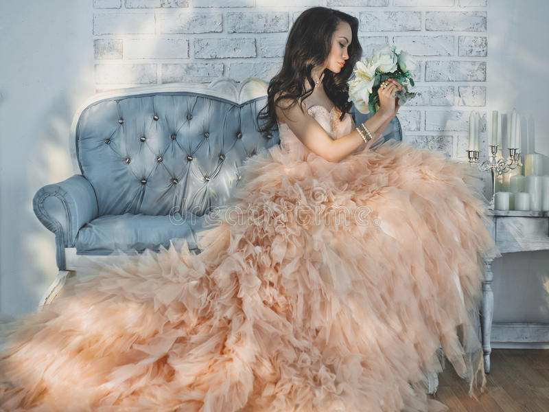 Beautiful lady in gorgeous couture dress on sofa. Fashionable portrait of beautiful lady in gorgeous couture dress on sofa. Holidays & Events. Evening dress royalty free stock photography