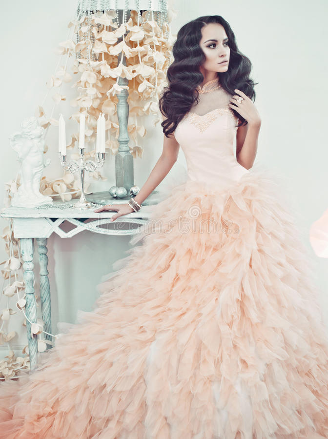 Beautiful lady in gorgeous couture dress in white interior. Fashionable portrait of beautiful lady in gorgeous couture dress in white interior. Holidays & Events stock image