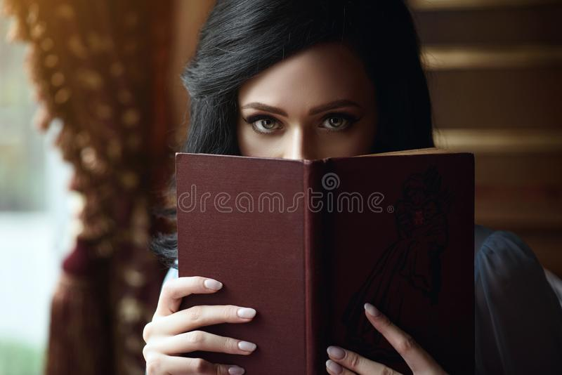 Beautiful lady hiding the part of her face behind the open book stock photo