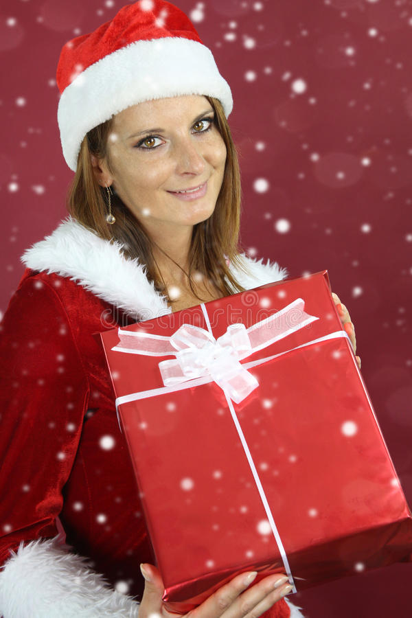 Beautiful lady holding a Christmas present. Over a red background royalty free stock image