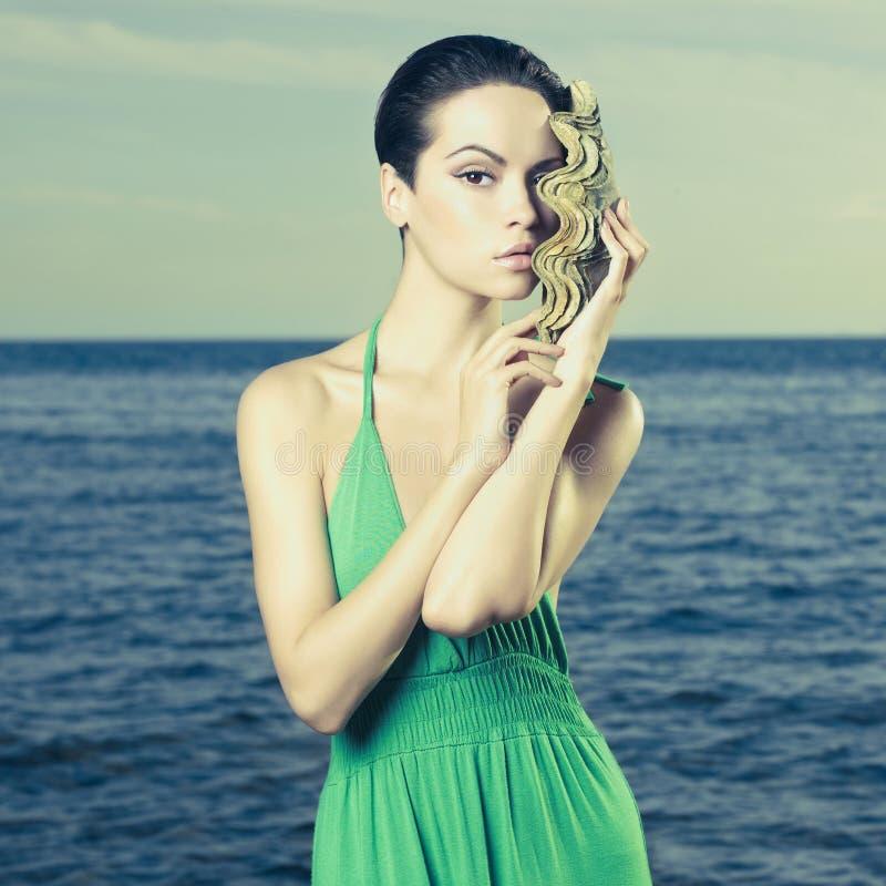 Beautiful lady with large sea shell. Portrait of a beautiful young lady with a large sea shell royalty free stock image