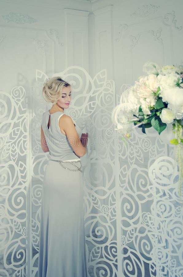 A beautiful lady in a long evening dress is standing in a bright room with a beautiful interior. Toning in the style of instagram stock photo