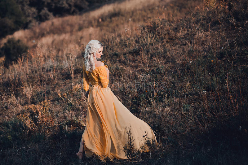 beautiful lady in a long yellow dress royalty free stock image