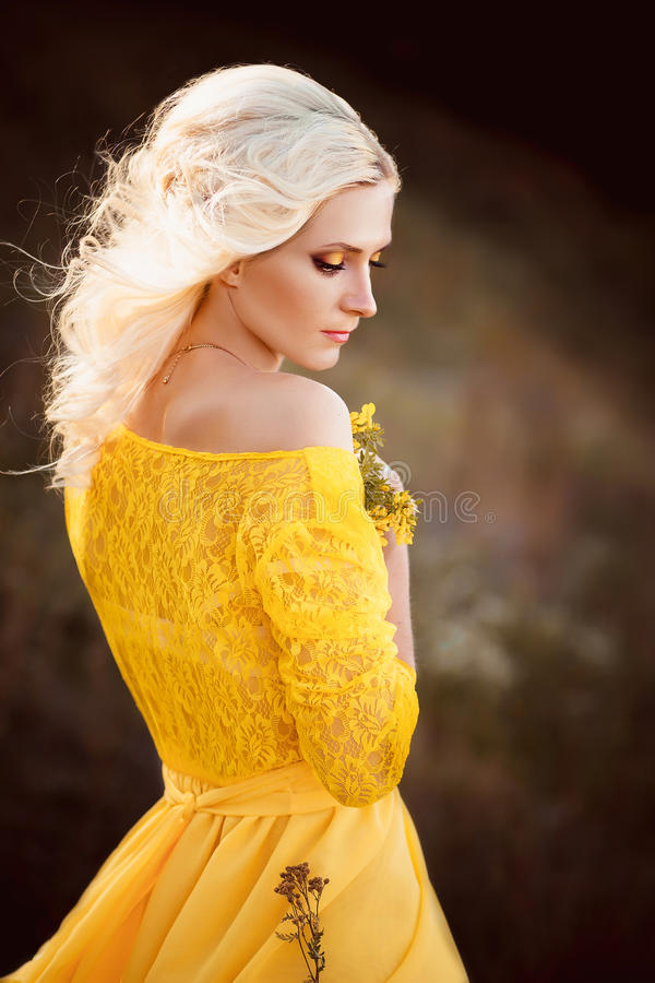 Beautiful lady in a long yellow dress royalty free stock photography
