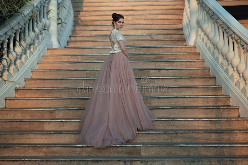 Beautiful lady in luxurious ballroom dress walking up the stairs of her palace. Baluster railing on both sides. Vintage concept royalty free stock photos