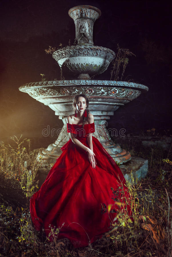Beautiful lady near the fountain. Beautiful lady dressed in red ball gown staying near the fountain stock photos