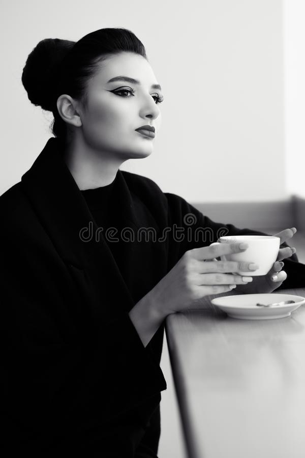 Beautiful lady with perfect make up and hair scrapped back into a high bun sitting at the bar and drinking coffee stock image