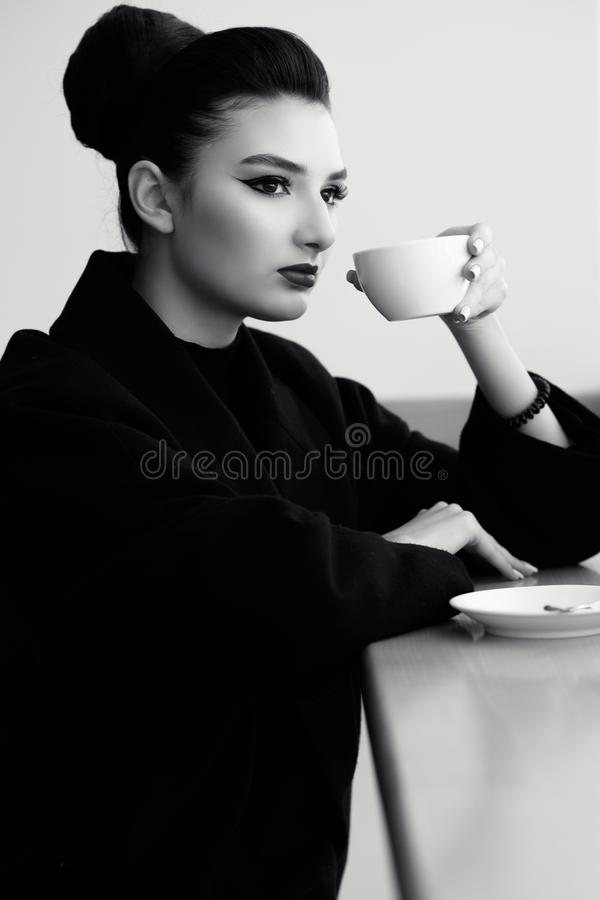 Beautiful lady with perfect make up and hair scrapped back into a high bun sitting at the bar and drinking coffee stock images