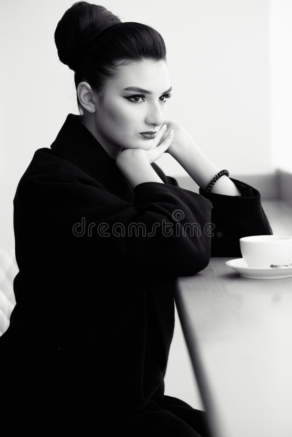 Beautiful lady with perfect make up and hair scrapped back into a high bun sitting at the bar putting her chin on hands royalty free stock image