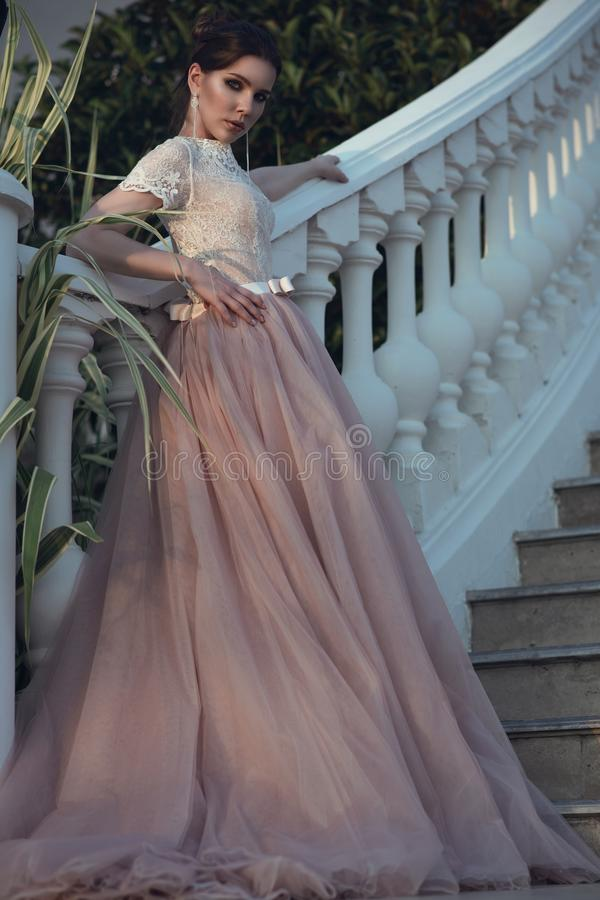 Beautiful lady with perfect make up in luxurious ballroom dress with tulle skirt and lacy top standing on stairs royalty free stock photos
