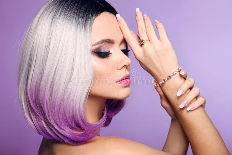 Beautiful lady presents amethyst ring and bracelet jewelry set. Woman portrait with ombre bob short hairstyle and manicured nails. Beauty makeup. Gorgeous stock photography
