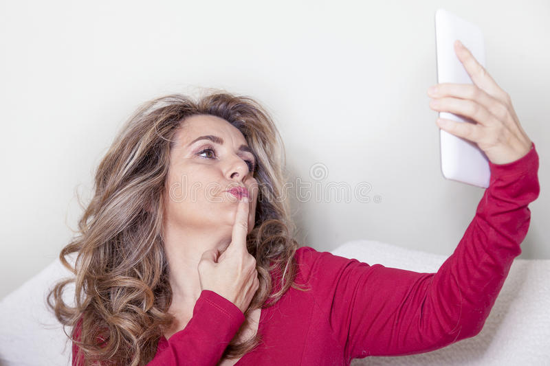 Beautiful lady with red dress takes a selfie. Indoor stock photography
