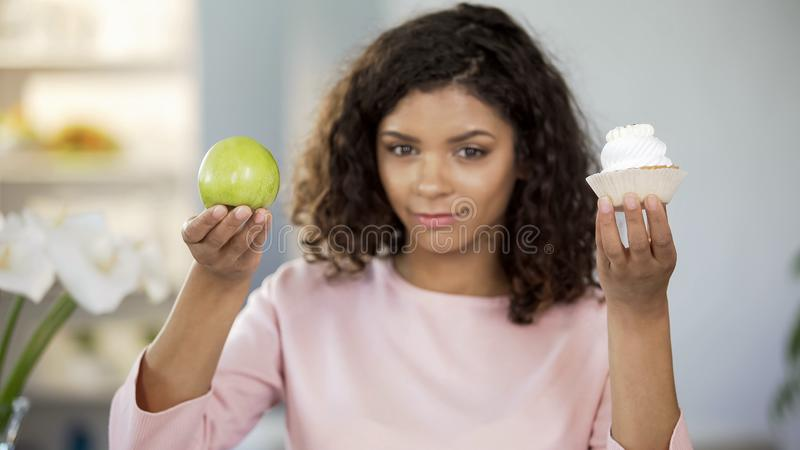 Beautiful lady showing cake and apple, food choice, healthy nutrition preference stock image