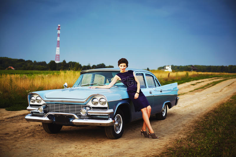 Beautiful lady standing near retro car. Retro woman posing with a retro car outdoors