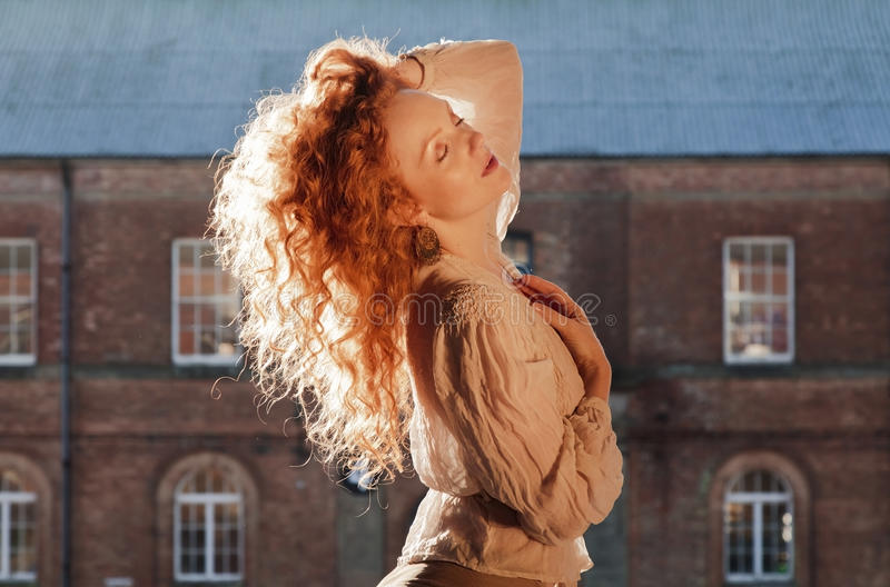 Beautiful lady with sunlight highlighting cascading long wavy red hair, hand holding hair on top of her head stock image
