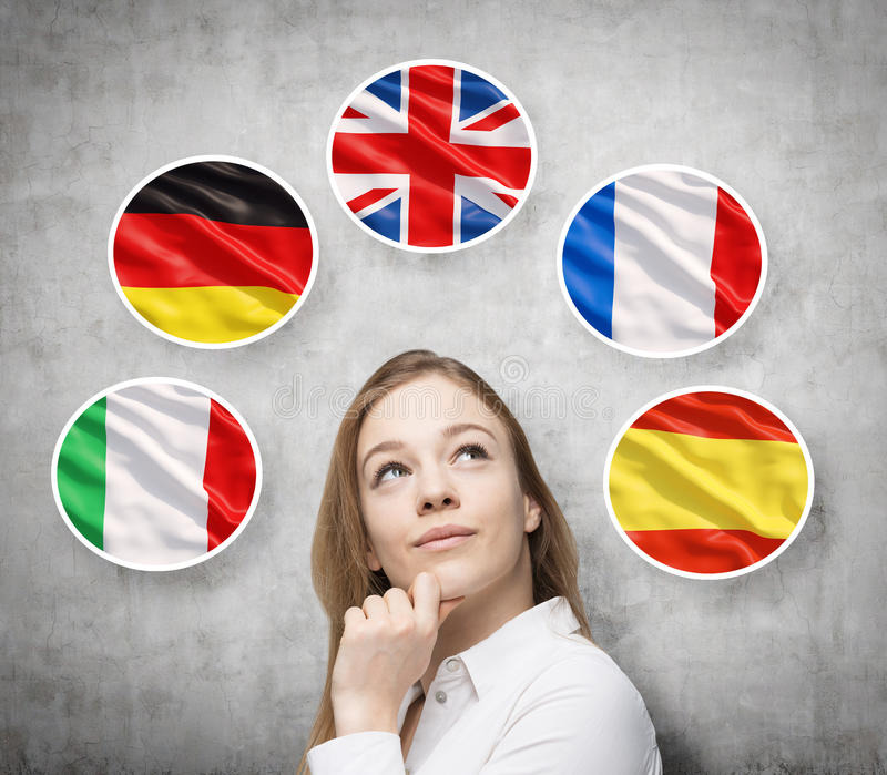 Beautiful lady is surrounded by bubbles with european countries' flags (Italian, German, Great Britain, French, Spanish). Learning of foreign languages concept stock photo