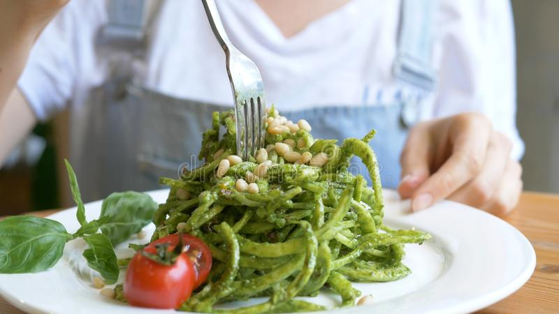 Beautiful lady tastes green fresh salad with tomatoes close royalty free stock photography