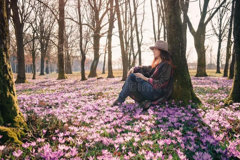 Spring.Crocuses.Forest.Fresh air. Inspiration. Female traveler. Beautiful lady traveler in a forest lit with sunshine, crocus aroma, fresh air that has got a royalty free stock photo