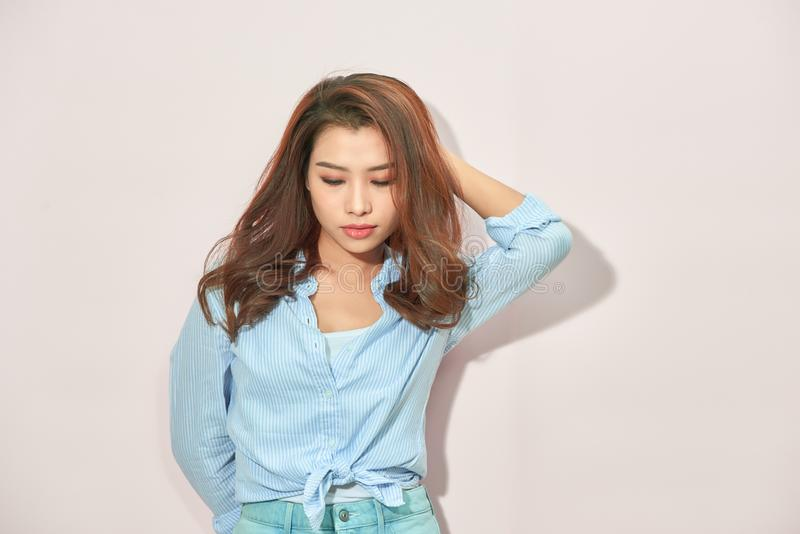 Beautiful lady in trendy blue blouse looking at camera with confident face expression while standing on light pink background stock image