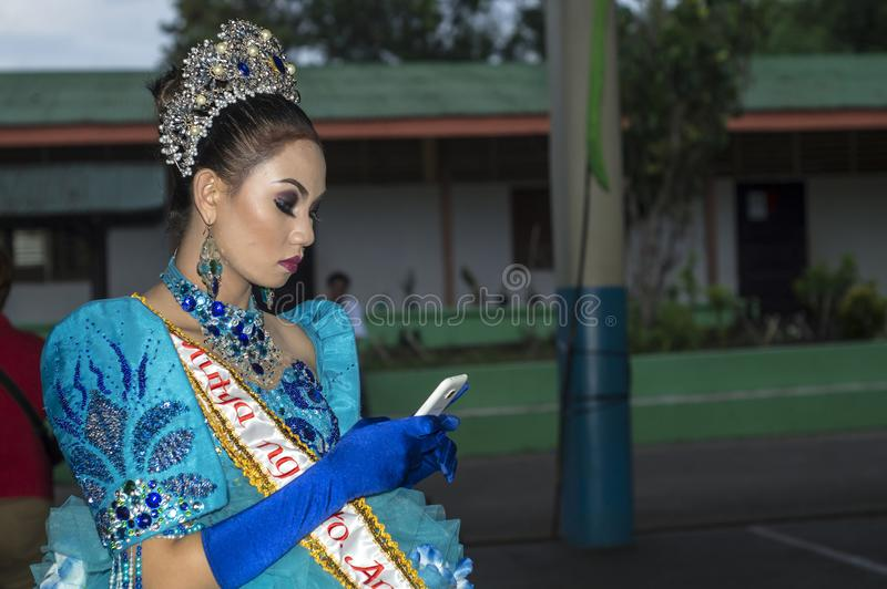Beautiful lady using smartphone before parade to honor the Virgin Mary. San Pablo City, Laguna, Philippines - May 28, 2016: Beautiful lady using smartphone stock photo