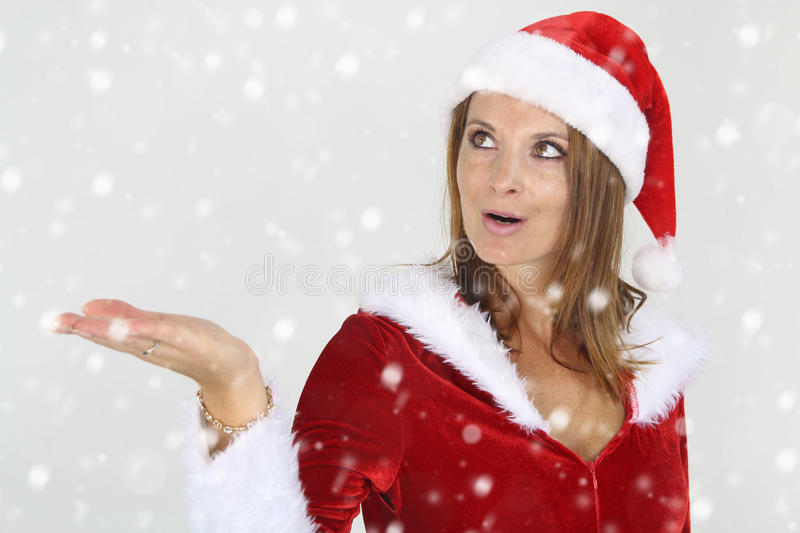 Beautiful lady watching the snow fall. Beautiful woman wearing a Santa Costume watching the snow fall royalty free stock images