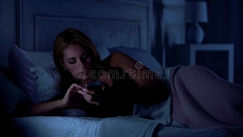 Beautiful lady writing messages on smartphone, dating site, gadget addiction. Stock photo stock photos