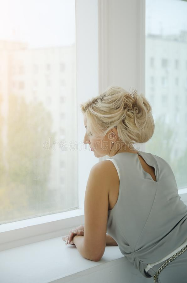A beautiful lady years in a long evening dress looks out the window. Toning in the style of instagram. Sunset of the setting sun royalty free stock photos