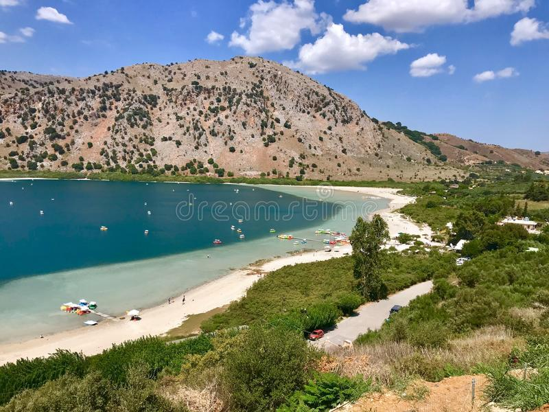 Beautiful lagoon with small passenger ferry and clear transparent water at southern part of Crete island, Greece. LOUTRO, CRETE - AUGUST 2018: Beautiful lagoon stock image