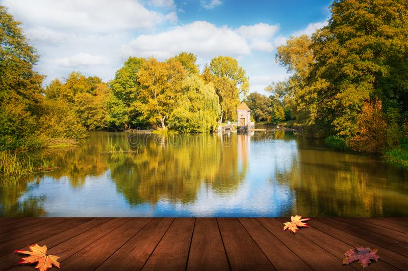 Beautiful Lake With Blue Cloudy Sky And Water Reflection - Table For Product Presentation In Foreground - Dam And Lodge In Backgro. Und stock image