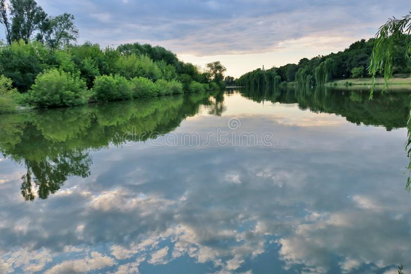 Beautiful lake with green trees whose branches fall into the water stock photos